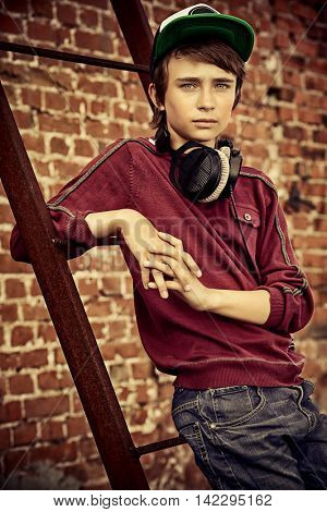 Modern teenage boy with headphones standing by a brick wall on the street. Modern generation. Summer holidays.