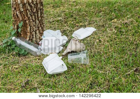 Heap of rubbish on grass in park, plastic and glass bottles and foam box , concept for environmental protection, littering of environment