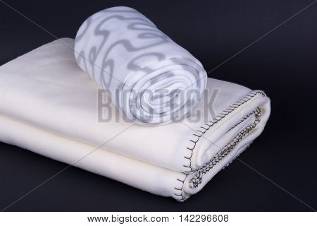 Two warm wool blankets on dark background