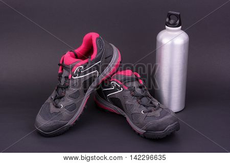 Women's hiking boots and water bottle on black background