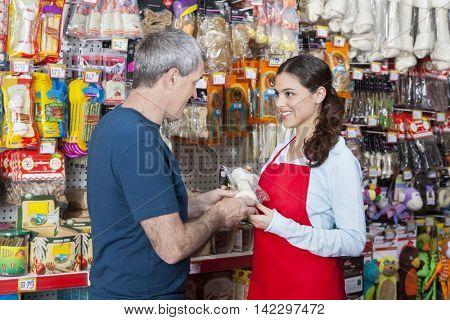 Smiling Saleswoman Showing Artificial Bone To Mature Man