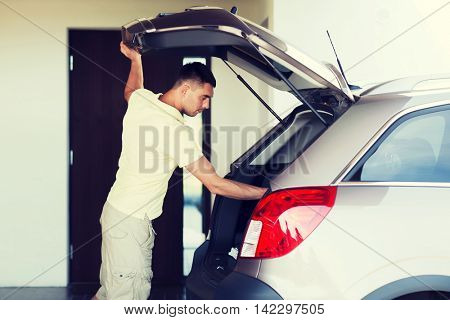 road trip, transport, private property leisure and people concept - young man with open car trunk at parking space