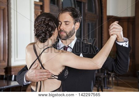 Man Closing Eyes While Performing Tango With Woman