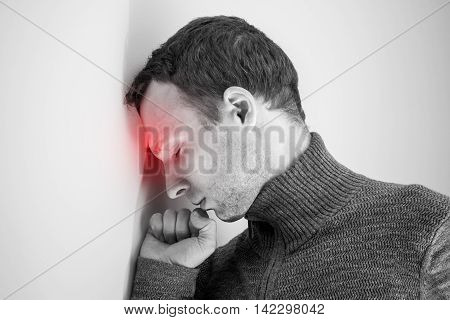 Young adult man with headache near white wall. Black and white stylized photo with red local ache spot