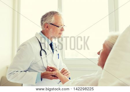 medicine, age, health care and people concept - doctor checking senior woman pulse at hospital ward