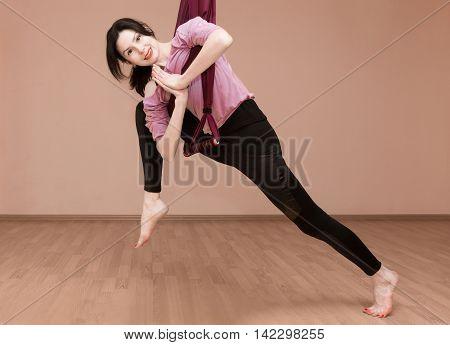 Woman making yoga exercises with hammock on the floor indoor