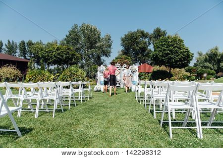 Rows of white folding chairs on lawn before a wedding ceremony in summer. Girl organizers suggest a final order before the guests arrive.