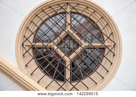 Round window with metal bars in the old house