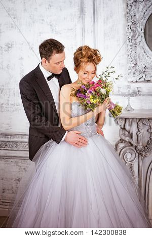 bride and groom in a luxurious gray interior. Bride smelling the flowers. groom looking at bride.