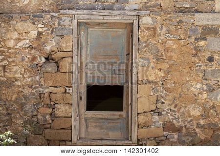 Old door in the stone walls of the village houses. Excellent background