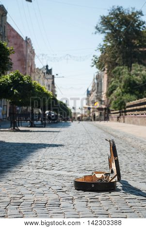 Cobbles on the street of the old town. Blurred background. In the foreground is an open case from the cello. Chernivtsi - an ancient city in western Ukraine