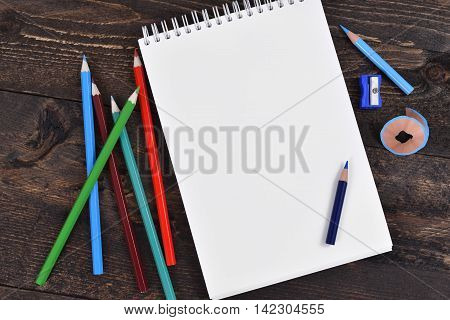 Note pad, pencils and sharpener an rustic wenge wood work desk