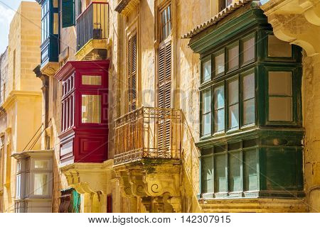 Traditional colorful Maltese balconies and wellow walls at Valletta, Malta