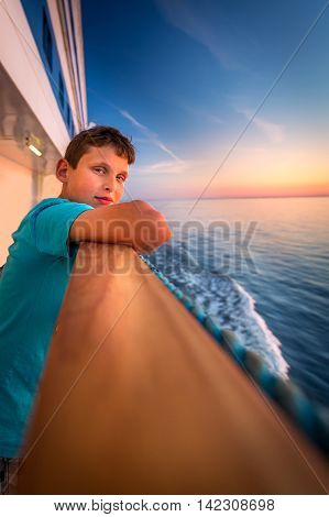 Boy at the railing of a cruise ship at sunset.