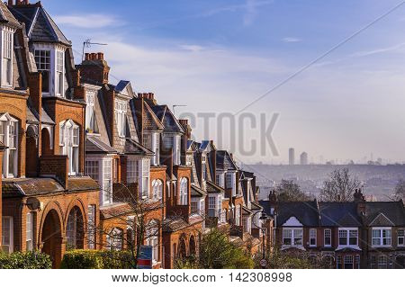 Typical British brick houses with panorama of London and blue sky - London, UK