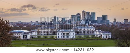Panoramic skyline view of Greenwich and national maritime museum and skyscrapers of Canary Wharf at sunset - London, UK