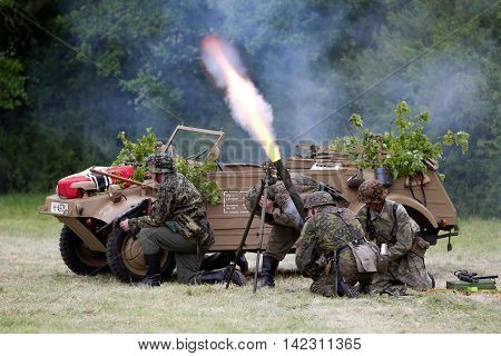 DENMEAD, UK - MAY 24: WW2 German army reenactors fire a blank mortar round towards the US lines during a battle re-enactment scene at the Overlord show on May 24, 2015 in Denmead.