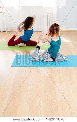 Portrait of two young women practicing one legged king pigeon, yoga practice, asana and meditation