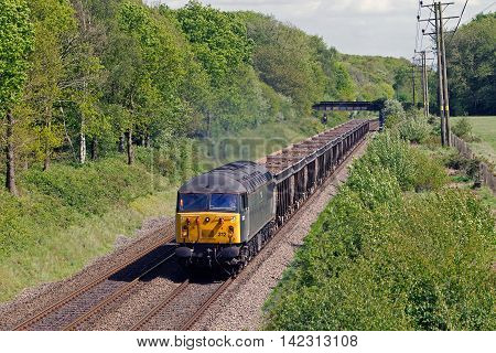 BEACONSFIELD, UK - MAY 9: A vintage class 56 diesel loco, built around 1976, leads a train of spoil waste from Londons Crossrail project to a suburban landfill site on May 9, 2014 in Beaconsfield