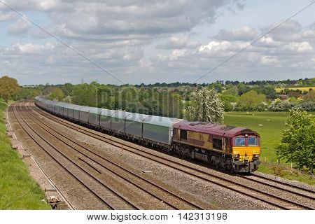 PANGBOURNE, UK - MAY 14: An EWS operated ferry wagon train passes Berkshire with a westbound freight train on May 14, 2014 in Pangbourne. EWS now owned by DBS is the largest UK rail freight operator