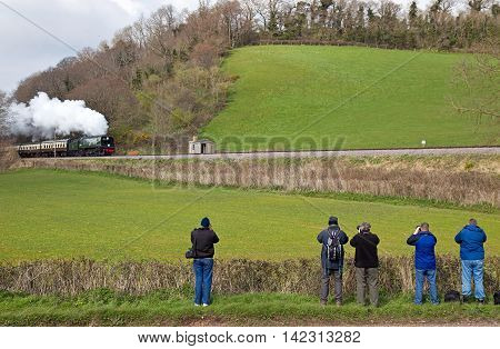WILLITON, UK - MARCH 27: Rail enthusiasts with cameras ready await the arrival of Light Pacific loco Manston at the foot of Castle Hill during the WSR spring steam gala on March 27, 2014 in Williton