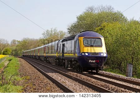 BEDWYN, UK - APRIL 30: A First Great Western operated HST approaches Hatchett Lane on April 30, 2014 in Bedwyn. FGW operate at 208 stations over an operating distance of 2130 km