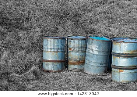 fuel drums on a background of black and white grass