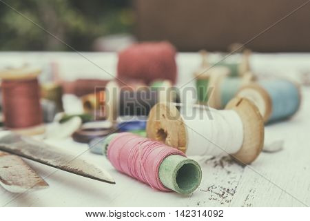 Set of several pied garment threads with scissors on a bright wooden background. Toned and processing photos with soft focus in vintage style.