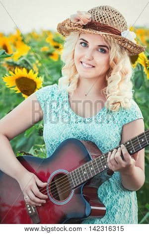 Portrait of a beautiful smiling blonde girl in a straw hat outdoors playing guitar