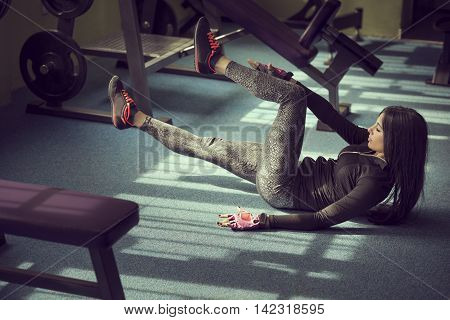 Attractive muscular young woman working out in a gym doing sit ups on the floor next to a weightlifting machines