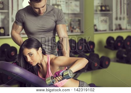 Attractive muscular young woman working out in a gym lifting weights while her instructor is supervising her efforts