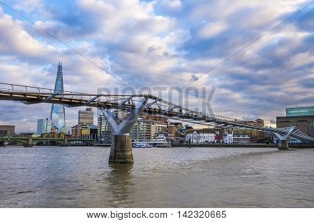 Millennium Bridge on River Thames with beautiful blue sky and clouds, skyscraper and museum at the background - London, UK