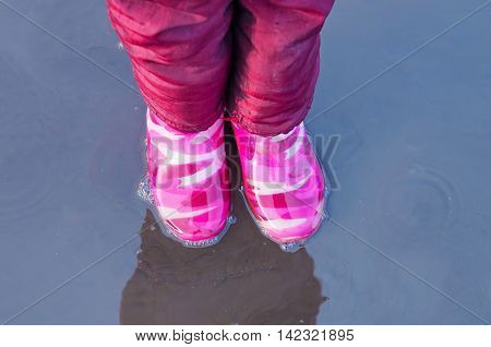 pair of feet in rubber boots child standing in a puddle