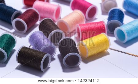 colorfull plastic yarn spools on white background