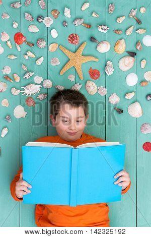 Cute Boy Reading Blank Book Near Seashells