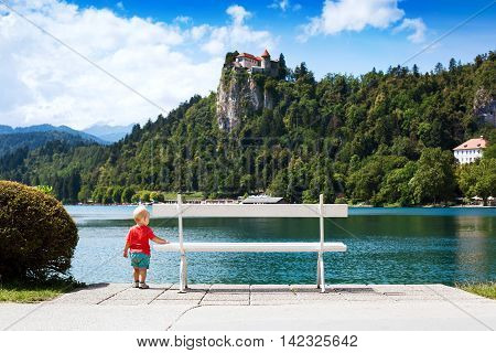 Cute Child Boy At Summertime On The Lake Bled And Bled Castle Background