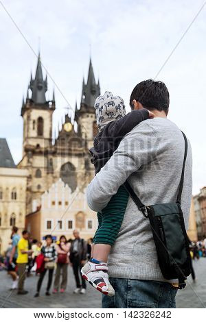 Family of Tourists: Father and him son on the Background of Church of Our Lady before Tyn at the Old Square in Prague Czech Republic. Concept of Travel and Explore of Europe.