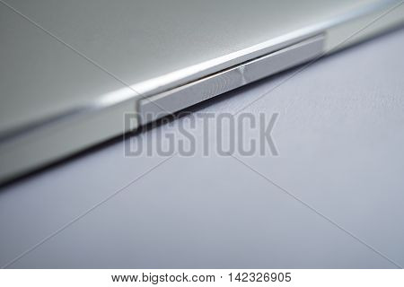 Macro detail of a silver rocker switch button made of brushed aluminum in the modern smart phone with shiny beveled edges