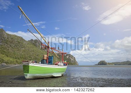 traditional fishing boat laying on a beach near the sea with mountain and island sunlight effect on the right side of picture colorful picture style wide angle