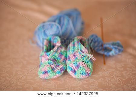 Knitted baby booties on a sofa hand made closeup