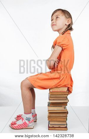 Schoolgirl sitting on books and looking up in surprise, sitting on a white background