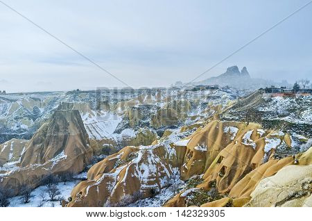 The amazing landscape of the Pigeon Valley covered with snow and the misty Uchisar rock on the background Cappadocia Turkey.