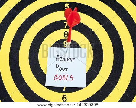 Handwriting Achieve your goals on notepaper with dart arrow and dart board. (Business concept)