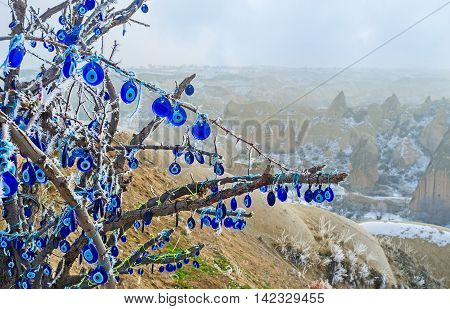 The branches of the old tree decorated with the eye-shaped amulets - Nazars made of blue glass and believed to protect against the evil eye Cappadocia Turkey.