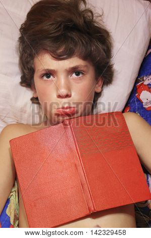 preteen boy close up photo with book in bed grimacing