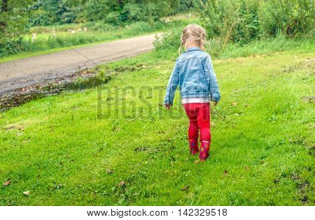 Little toddler girl with blonde pigtails en red boots walking through the wet grass. Her pants are dirt from splashing in the puddles.