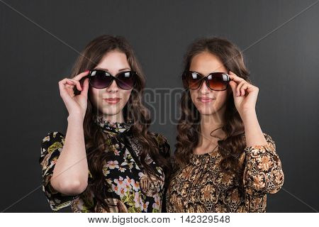 Two beautiful happy girls in sunglasses on the grey background. Young active people.
