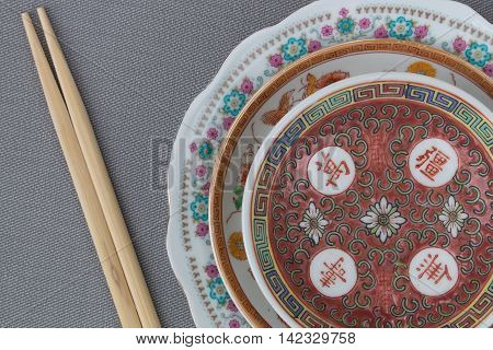 Closeup of Chinese porcelain plates and chopsticks top view in studio shot
