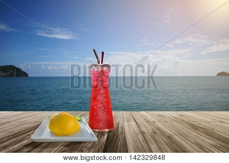 red soda and orange sponge cake on Wooden table front of blurred background. Perspective brown wood over blur sea and blue sky with cloud summer season. sunlight effect on right side of picture