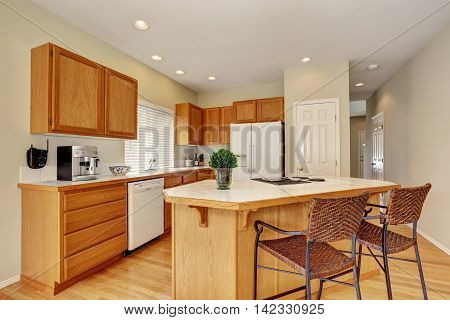 Light Wooden Kitchen Interior With Kitchen Island And Wicker Stools